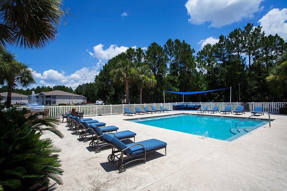 Tall, tropical trees surround the modern swimming pool and poolside chairs at Crystal Lake Apartments in Pensacola, FL